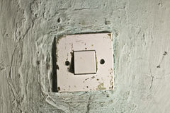 Old dirty light switch on old cracked wall Royalty Free Stock Photography