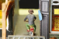 Old and dirty miniature plastic figure model ride bicycle. Royalty Free Stock Photos