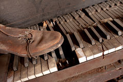 Old Dirty Piano With Old Leather Shoe Royalty Free Stock Photography