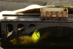 Railroad model on bridge. An old and dirty plastic goods wagon train toy model on bridge model scenery represent the train toy for hobby and collection concept royalty free stock images