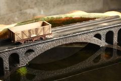 Railroad model on bridge. An old and dirty plastic goods wagon train toy model on bridge model scenery represent the train toy for hobby and collection concept royalty free stock photos