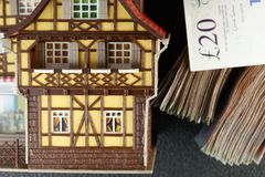 Old and dirty plastic house model put beside banknote. Royalty Free Stock Photography