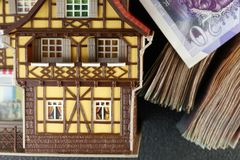 Old and dirty plastic house model put beside banknote. Stock Photos