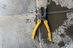 Old dirty pliers. On ground and wet for use in Stock Photography