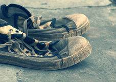 Old dirty retro gym shoes on grunge a background. Old sports shoes. Royalty Free Stock Photography