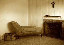 Old dirty room in sepia. Run down room with old sofa and travel bag. There is also a fireplace and a crucifix hanging above the shelf which has two books on it Royalty Free Stock Photos