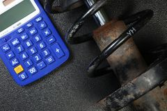 The old and dirty shock absorber cover with rust put beside calculator scene. Royalty Free Stock Photography