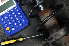 The old and dirty shock absorber cover with rust put beside calculator scene. Stock Photo