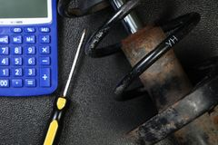 The old and dirty shock absorber cover with rust put beside calculator scene. Stock Images