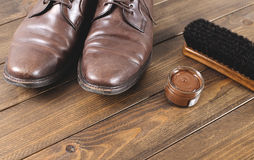 Old dirty shoes next to cleaning products on brown wooden table with. Copy space. Stock Images