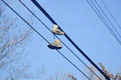Old dirty shoes thrown over power lines Stock Photo