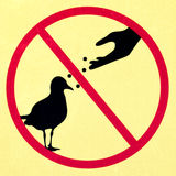 Old Dirty Sign with symbol signifying DO NOT FEED BIRDS Royalty Free Stock Photos