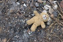 Old dirty teddy bear neglected on the ground soil. End of childhood stock image