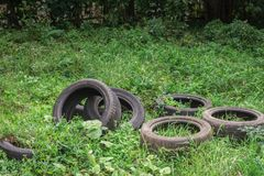 Old dirty tires pollute nature stock image