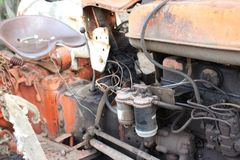 An old and dirty tractor that is abandoned. A very old tractor has a very damaged engine Royalty Free Stock Photos