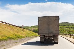 Old dirty truck goes on rural road, rear view. Old dirty truck goes on rural road in sunny day, rear view Stock Image