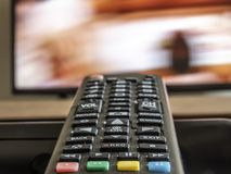 Old and dirty tv remote control. With TV background with selective focus royalty free stock photos