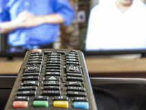 Old and dirty tv remote control. With TV background with selective focus royalty free stock image