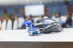 Old dirty VGA  tech cable  connector of computer on table white Blur meeting room background.  Royalty Free Stock Photo
