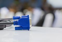 Old dirty VGA  tech cable  connector of computer on table white Blur meeting room background.  Royalty Free Stock Images