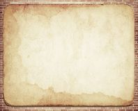Old dirty vintage  parchment with stained texture. On brown brick wall Stock Photo