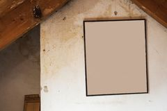 Old dirty wall in abandoned attic with a blank painting, space for text grunge broken concrete background texture. Vintage design old stock photo