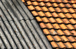 Old dirty weathered wavy slate and ceramic tiles shingle roof. Background Stock Image