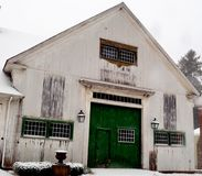 Old dirty white New England barn with green doors and multi-panel doors. Multi - storied, grimes, snow covered yard and bushes Royalty Free Stock Photography