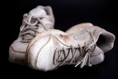 Old dirty white sneakers on black background. Stock Photography