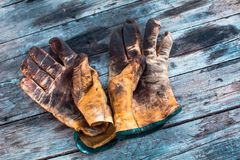 Old dirty work gloves on a wooden table stained with grease and oil royalty free stock photography