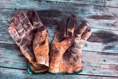 Working gloves over wooden table,  gloves for each finger. Old and dirty working gloves over wooden table,  gloves for each finger. Rural lifestyle concept royalty free stock photography