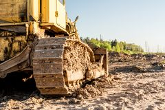 Free Old Dirty Yellow Crawler Bulldozer, Rear View, The Construction Machine Is Lit By The Rays Of The Setting Sun Stock Image - 116132631