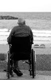 Old disabled man on wheelchair. Old disabled man sitting on wheelchair and looking at the sea Stock Photography