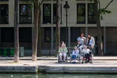 Old women in wheelchairs and their young aides Royalty Free Stock Photo