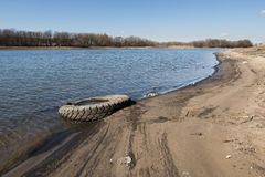 Old discarded car tire lying on the sandy bank of the river. royalty free stock photography