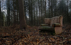 An old discarded Chair is dump illegaly in the middle of a woodland. Fly-tipping . An old discarded Chair is dump illegaly in the middle of a woodland stock photography
