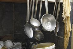 Bad public canteen kitchen. Old dishes, colander, pegs, scoops. public catering point, unsanitary conditions old badly washed dishes Royalty Free Stock Photography