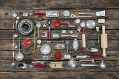Old dishes and cutlery on a wooden background in red, silver and Stock Images