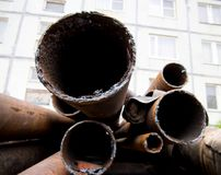 Old dismantled pipes of the heating system in the courtyard of a multi-storey building.  Royalty Free Stock Photos