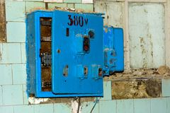 Old dismantled and rusty electrical panel assembly. On an abandoned and destroyed factory against a backdrop of chaos. Destruction and vandalism. Ukraine stock photos
