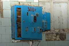 Old dismantled and rusty electrical panel assembly. On an abandoned and destroyed factory against a backdrop of chaos. Destruction and vandalism. Ukraine royalty free stock photography