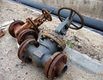 The old dismantled valves of the heating system lie near the trench.  Stock Photos