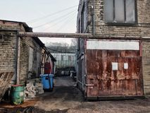 Old disused industrial buildings with chemical containers. And rusty decayed steel doors Stock Photography