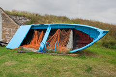 Old disused timber built fishing boat with nets and lobster pots on display stock photos