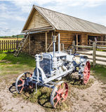 Old disused tractor. And rural detached wooden house in the forest area Royalty Free Stock Images