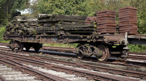 Old disused train wagon loaded with worn wooden sleepers Royalty Free Stock Photos