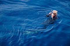 A Old Diver is Floating, (Koh Tao, Chumphon). A man who prepare to diving in the blue ocean in Tungku diving area is South-west area of Koh Tao (The popular Stock Image