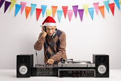 Old DJ with a christmas hat playing music. Against a wall with decoration flags royalty free stock photography