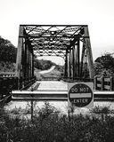 The Old Do Not Enter Bridge. Black and white shot of an old bridge with steel girders that has been bypassed and now has guardrails at either end with signs Royalty Free Stock Image