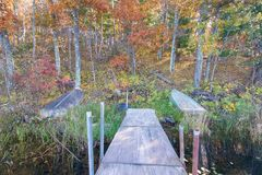 Old dock and boat on small remote lake in Northern Wisconsin with fall trees and fall color on shoreline stock image